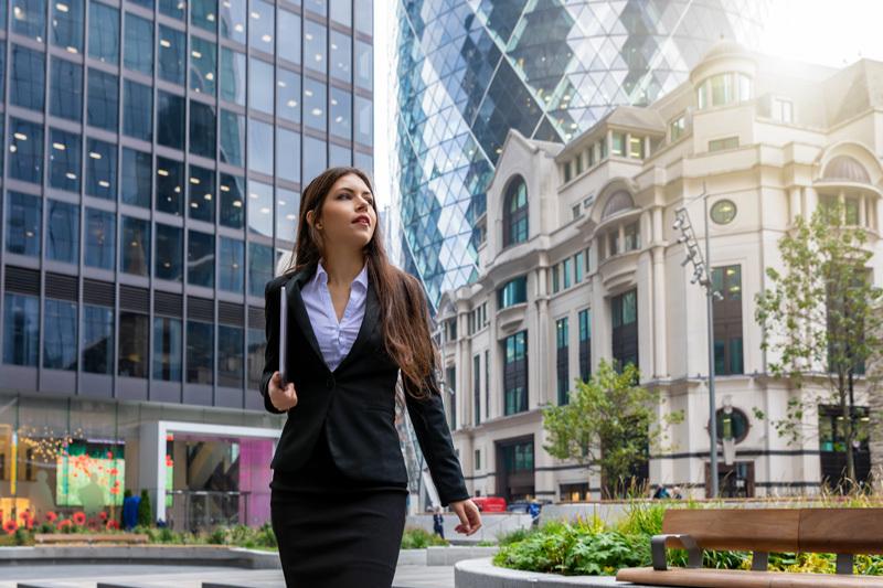 Young woman walking among City of London buildings