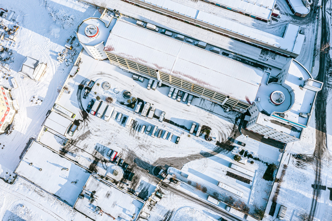 Aerial view of snow covered rooftops and parking lot demonstrates why we need climate change provisions for resilient building design