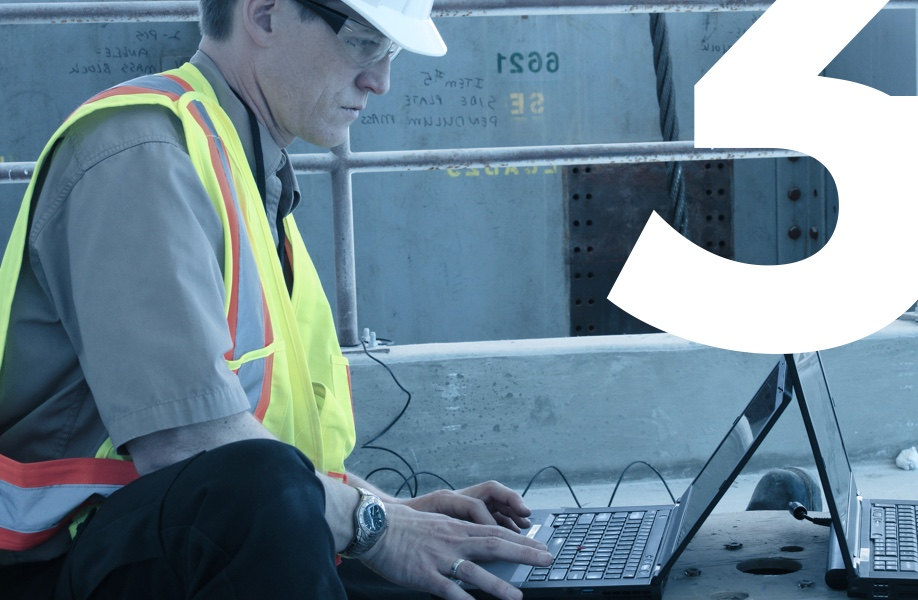 Image of team member working on a laptop at a construction site wearing yellow vest